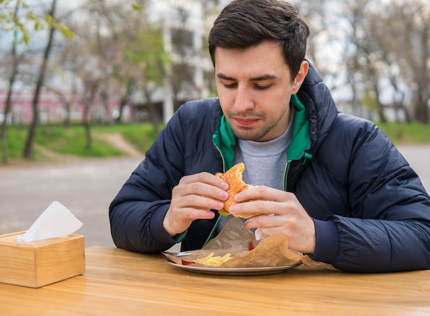 Man eating a burger in street food cafe