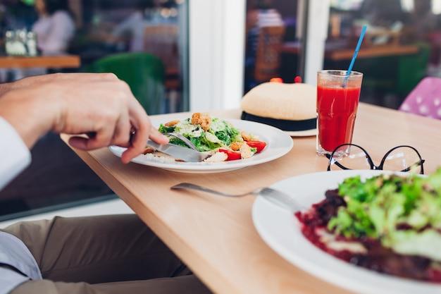Человек ест салат цезарь и томатный сок в ресторане. вкусный обед. концепция здорового питания.