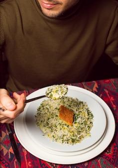 Man eating chigirtma sebzi plov, rice garnish with vegetables and herbs