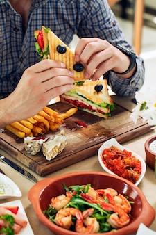 Man eating club sandwich in a restaurant.