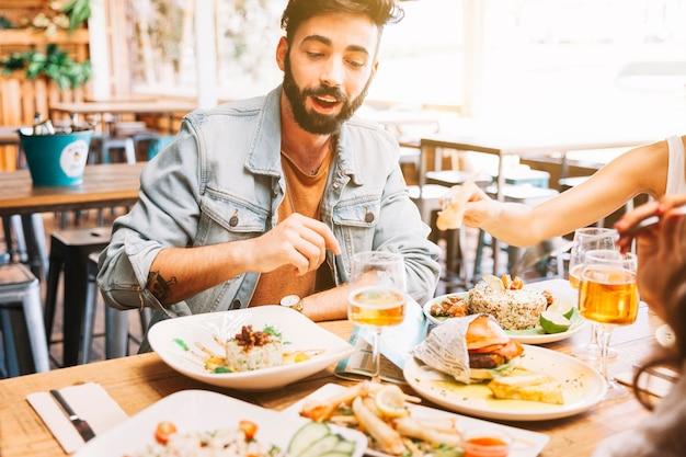 Мужчина ест разные блюда из пищи