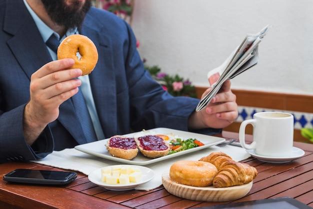 Мужчина ест пончик в ресторане