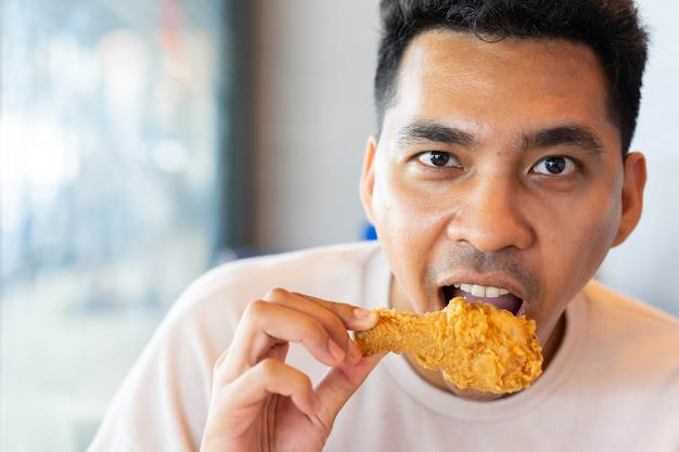 Man eating  fried chicken leg in brunch meal at restaurant with happiness in relax time