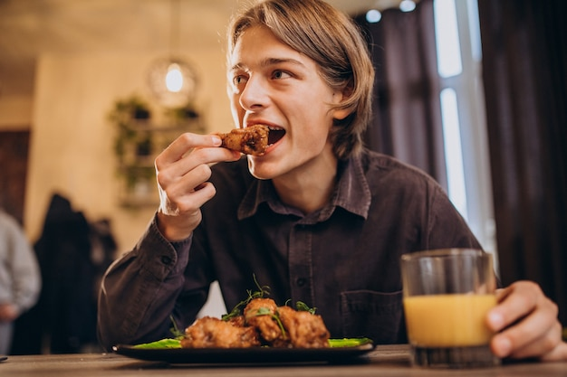 Man eating fried chicken with sauce in a cafe