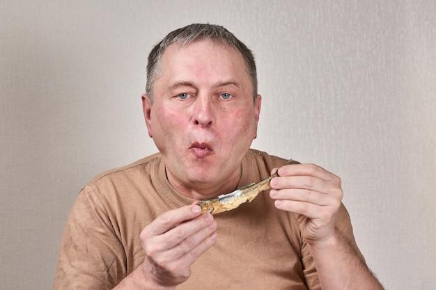 Человек ест жареную рыбу-корюшка, держа рыбу руками перед лицом