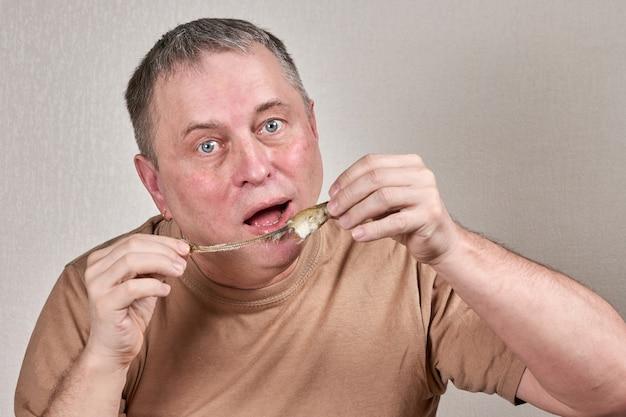 얼굴 앞에서 손으로 생선을 들고 튀긴 빙어를 먹는 남자