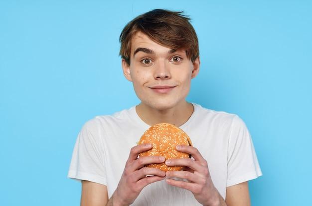 Man eating hamburger in white tshirt diet food lifestyle blue background