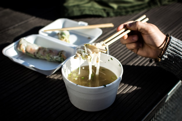 Man eating his take away vietnamese food with chopsticks outside