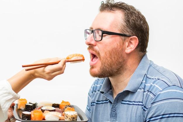 젓가락으로 나기 리 연어를 먹는 남자