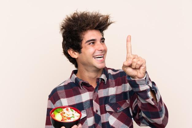 Человек ест лапшу на изолированной стене