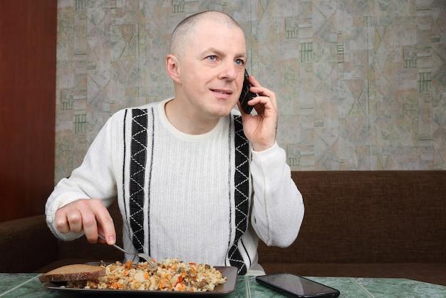 Человек ест плов и разговаривает по мобильному телефону