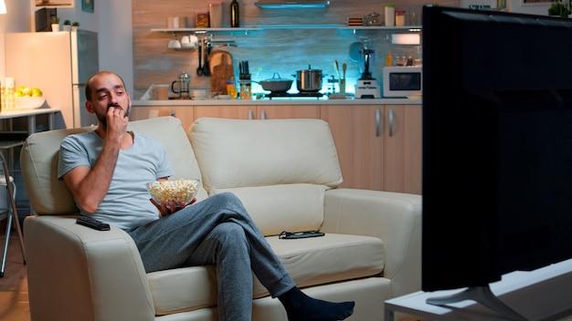 ポップコーンを食べてテレビを見ながら、深夜のおやつを楽しんでいる男性。ポップコーンを食べてホームシネマでエンターテインメントテレビ番組を見ながら夜遅くソファに横たわってリラックスした男