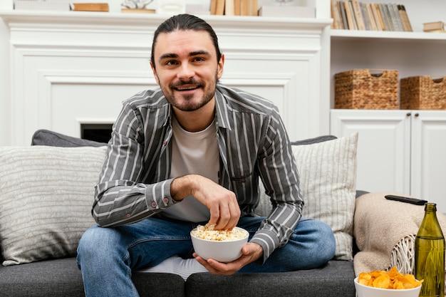 Человек ест попкорн и смотрит телевизор, вид спереди