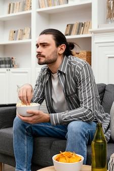 Человек ест попкорн и смотрит телевизор, вид сбоку