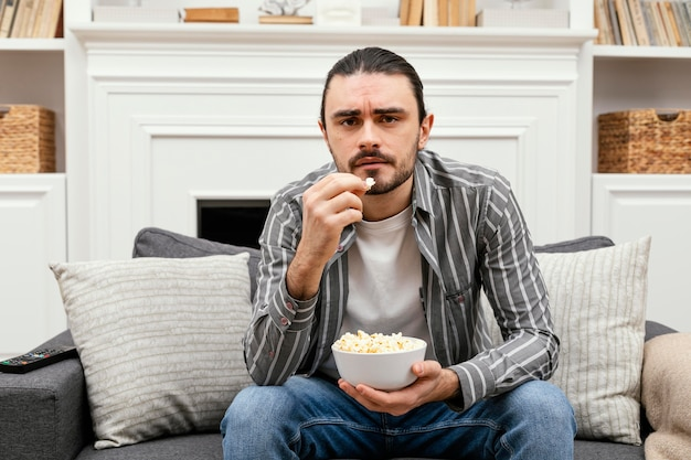 Человек ест попкорн и смотрит телевизор