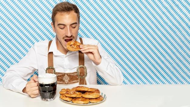 Man eating pretzels with black beer