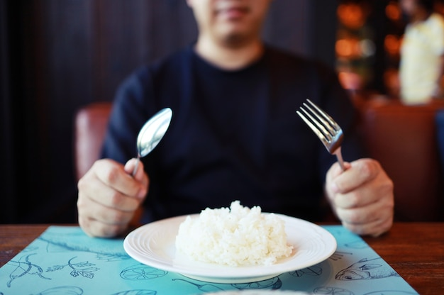 Man eating rice enjoying a meal in restaurant.