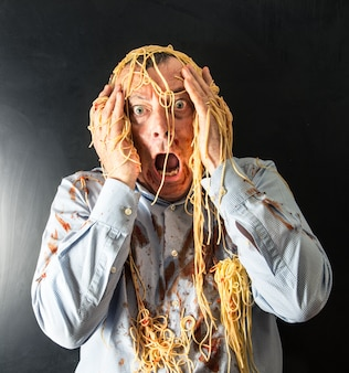 Man eating spaghetti with tomato sauce in head