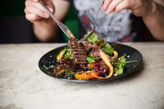 グリルビーフとステーキサラダを食べる男。ルッコラ;にんじんと種。健康食品
