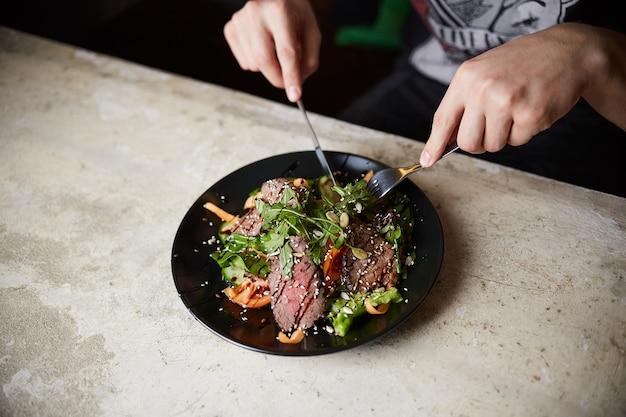 구운 쇠고기와 스테이크 샐러드를 먹는 남자; 아루 굴라; 당근과 씨앗. 건강한 음식
