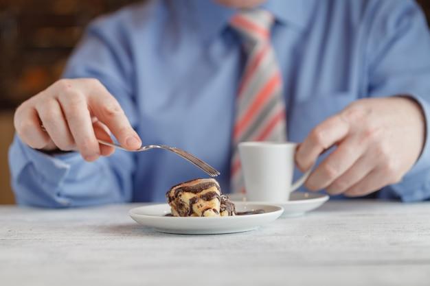 Человек ест клубничный чизкейк в кафе, пить кофе
