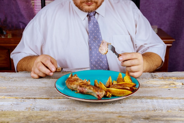 Man eating strip steak served with loaded baked potato with roasted steaks at restaurant