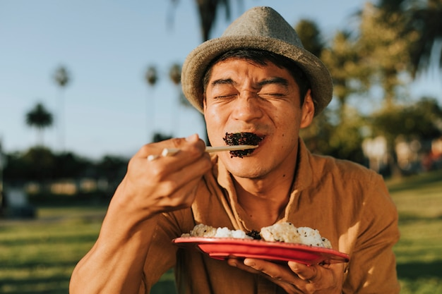 Man eating sushi in the park