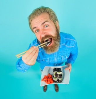 Мужчина ест суши суши человек с суши в палочке для еды доставка суши из японии японская еда маринованный имбирь