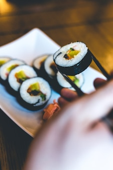 Man eating traditional korean gimbap rice rolls with chopsticks