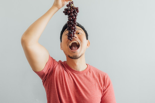 Man eats bunch of red grapes.