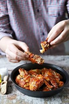 남자는 닭 날개를 먹는다.