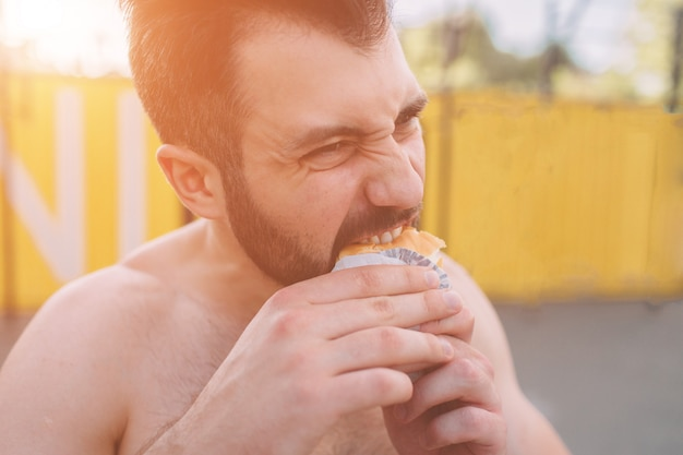 Man eats a hamburger after a workout