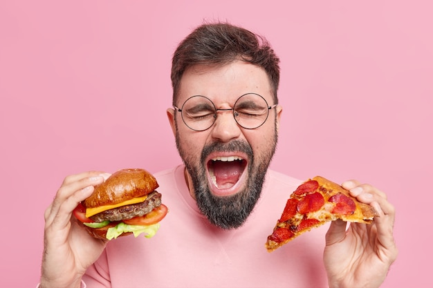 Man eats junk food shouts loudly keeps mouth widely opened holds burger and slice of pizza expresses negative emotions wears round spectacles casual jumper. binge eating concept