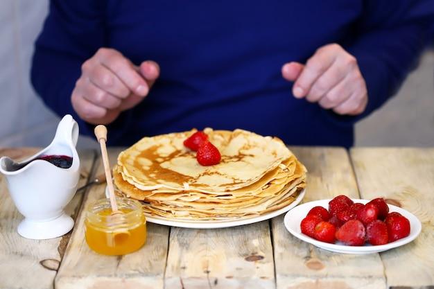 男は手でパンケーキを食べます。木製のテーブルの上にパンケーキ、イチゴ、蜂蜜、ジャムのプレート。パンケーキウィーク。
