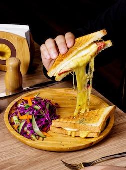 L'uomo mangia il panino servito con insalata