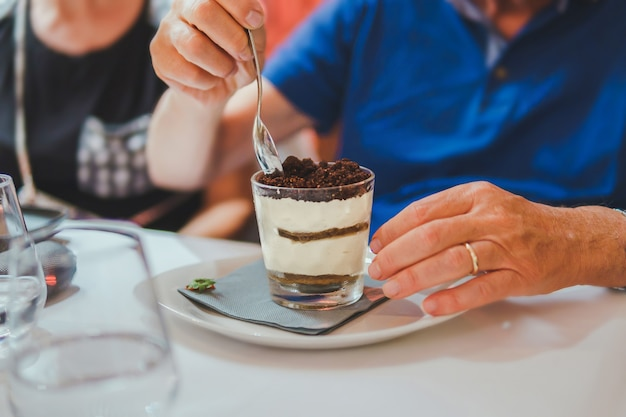 A man eats tiramisu in a glass glass