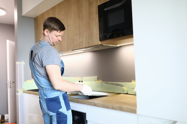 Man electrical repairs kitchen surface apartment
