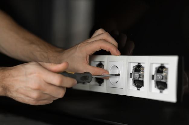 Рука электрика человека с отверткой, разбирающей белую электрическую розетку на черной стеклянной стене