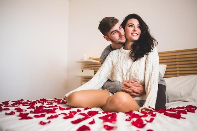 Человек обнимает за своей подругой в постели с лепестками