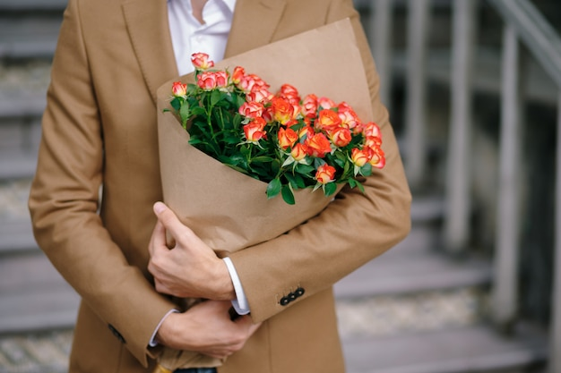 Man embracing a bouquet of flowers, folded in craft paper.