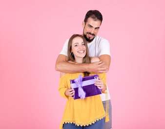 Man embracing her girlfriend holding purple gift box over pink background