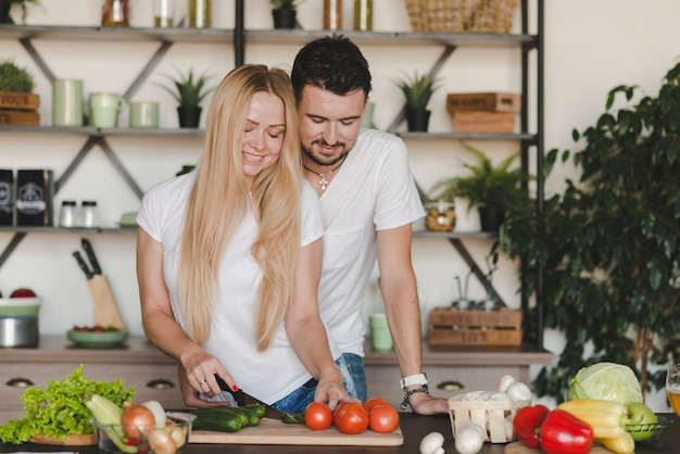 Man embracing her wife cutting vegetables on kitchen counter
