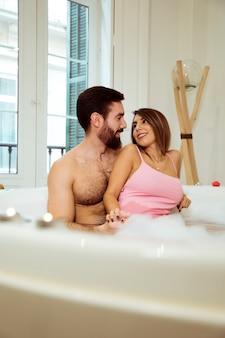 물과 거품 스파 욕조에 웃는 여자를 수용하는 사람