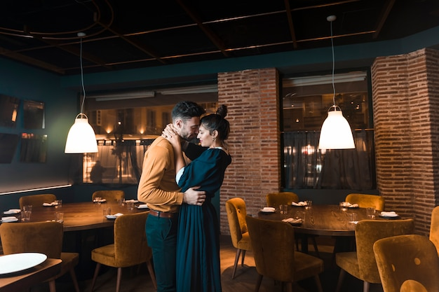 Man embracing with woman in restaurant