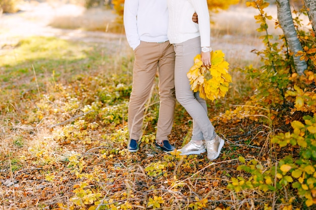 Man embracing woman in the autumn forest woman holding a wreath of yellow leaves in her hands