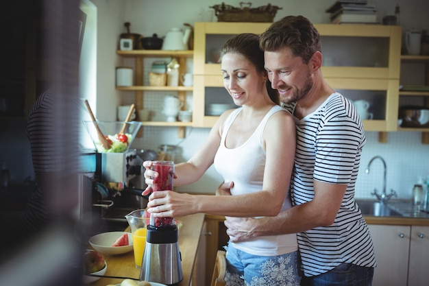 Man embracing woman from behind while preparing watermelon smoothie in the kitchen