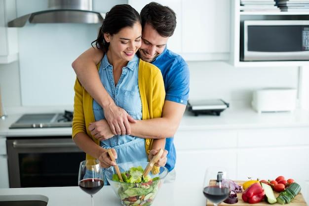 自宅のキッチンで女性を抱きしめる男