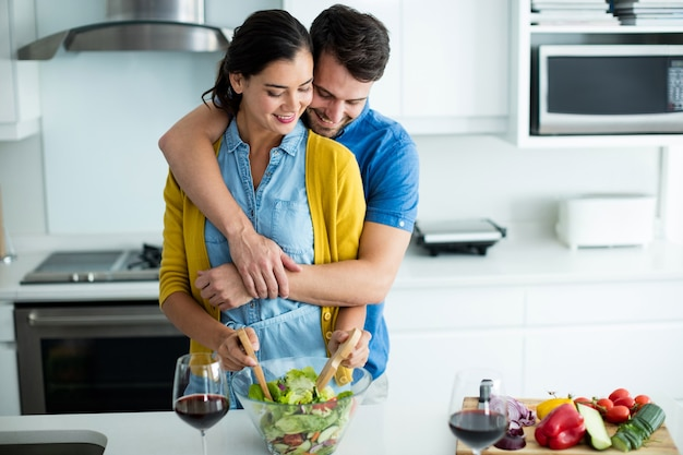 Man embracing woman in the kitchen at home