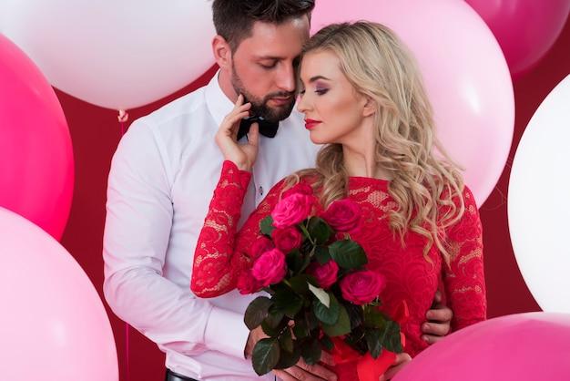 Мужчина обнимает женщину с красными розами
