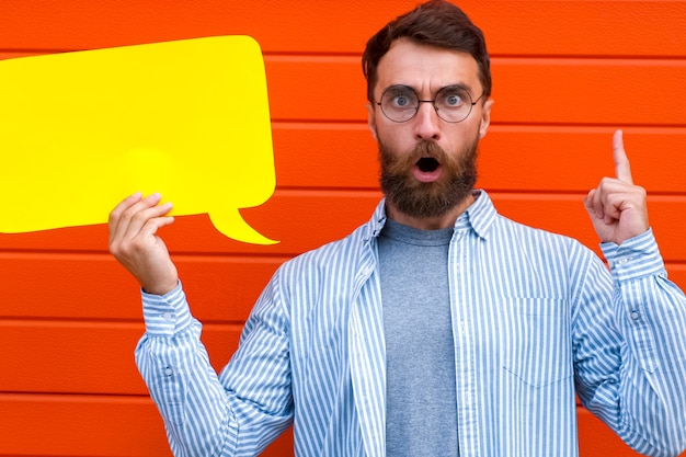 Man emotion face holding speech bubble looking at camera